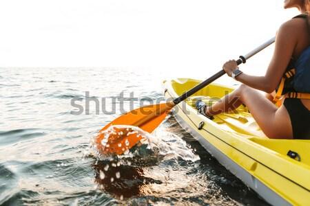 Handsome man kayaking on lake sea in boat. Stock photo © deandrobot