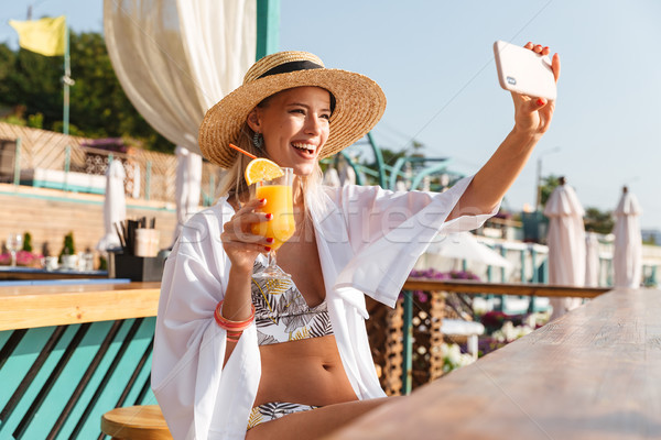 Photo of beautiful blond woman 20s in straw hat and swimwear tak Stock photo © deandrobot