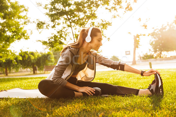 Image of smiling sportswoman 20s wearing headphones working out  Stock photo © deandrobot