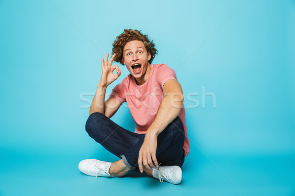 Portrait of a cheerful young curly haired man showing ok Stock photo © deandrobot