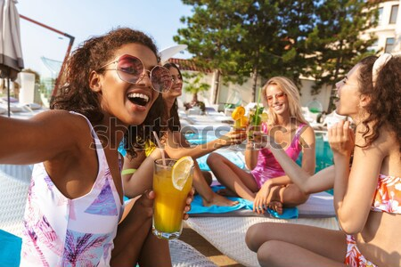 Image of four cheerful young women in swimwear Stock photo © deandrobot