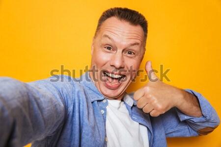 Portré mérges középkorú férfi izolált citromsárga arc Stock fotó © deandrobot