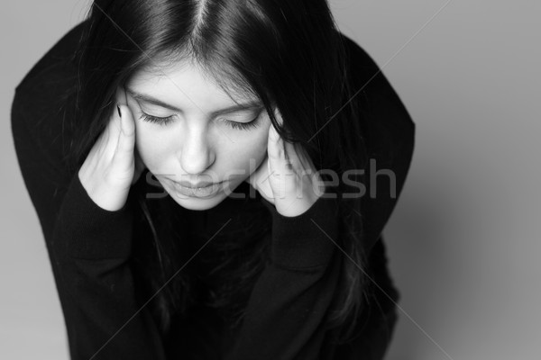 Black and white photo of a thoughtful young woman with hands over her head Stock photo © deandrobot