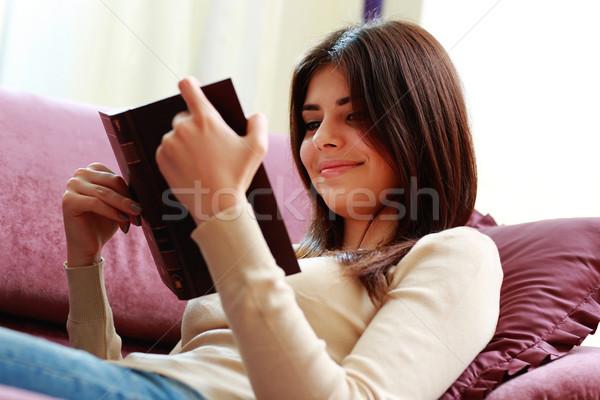 Stockfoto: Jonge · glimlachende · vrouw · sofa · lezing · boek · home