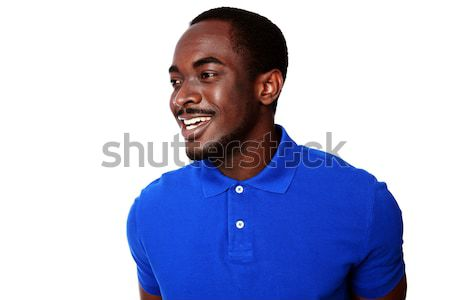 Portrait of a happy african man looking away over white background Stock photo © deandrobot