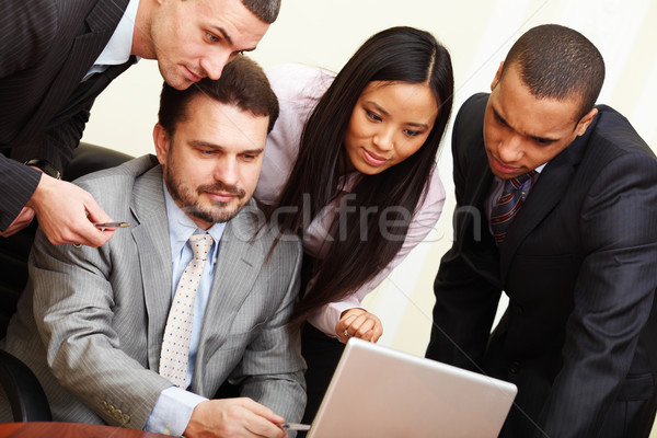 Mature businessman shows something on laptop to his multi ethnic business team Stock photo © deandrobot