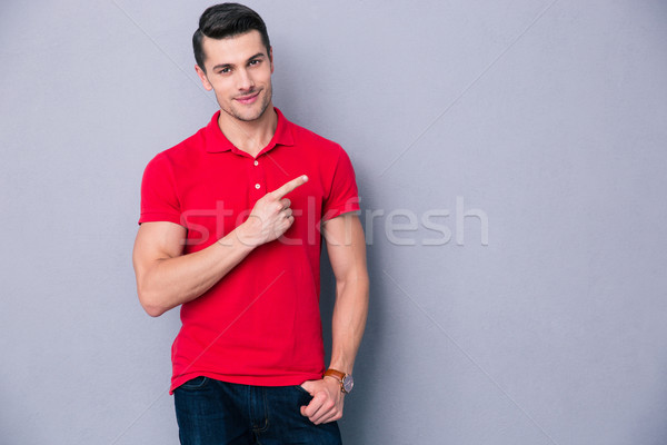 Portrait of a casual man pointing away Stock photo © deandrobot