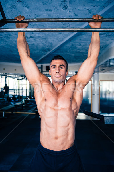 Muscular handsome man pulling up Stock photo © deandrobot