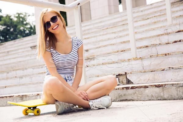 Female skater sitting on skate outdoors Stock photo © deandrobot