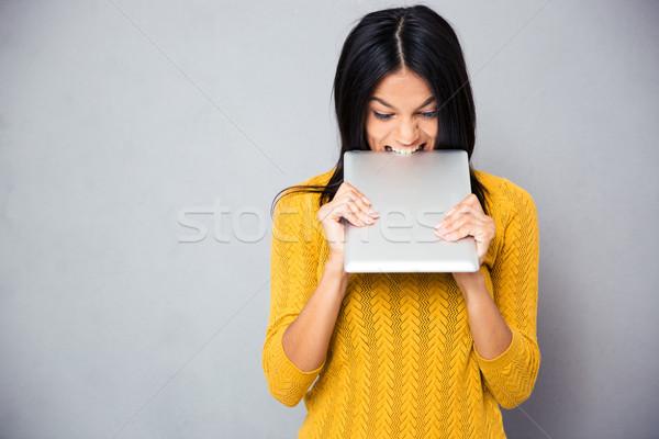 Mérges nő harap táblagép szürke diák Stock fotó © deandrobot