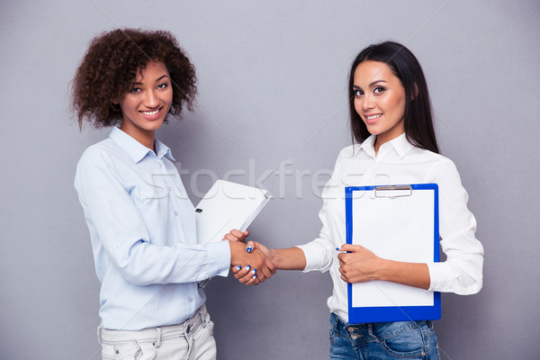 Two woman making handshaking Stock photo © deandrobot