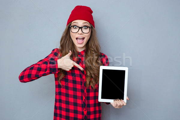 Woman pointing finger on tablet computer screen Stock photo © deandrobot