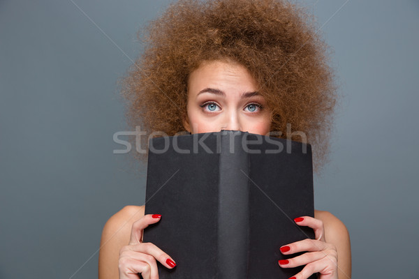 Pretty young curly woman hiding a book Stock photo © deandrobot