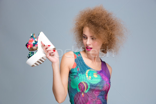 Curly woman stares at colorful summer shoe with white platform Stock photo © deandrobot