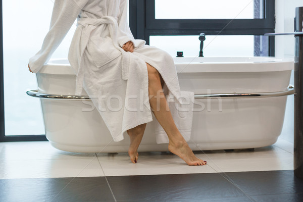 Attractive young barefooted woman in white bathrobe sitting on bathtub  Stock photo © deandrobot