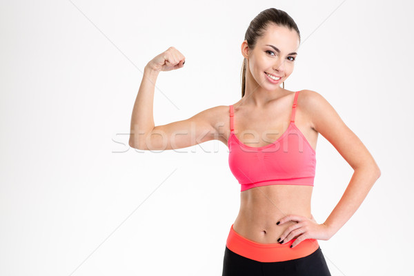 Smiling sports woman showing her bicep Stock photo © deandrobot