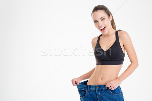 Fitness woman showing that jeans became too big for her  Stock photo © deandrobot