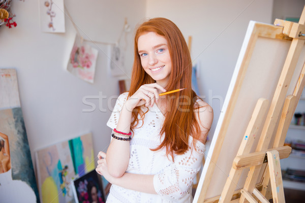 Cheerful attractive young woman artist painter sketches by pencil  Stock photo © deandrobot