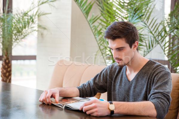 Férfi olvas magazin étterem portré fiatalember Stock fotó © deandrobot