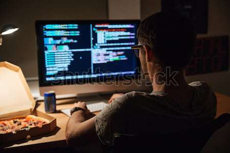 Stock photo: Concentrated software developer eating pizza and coding