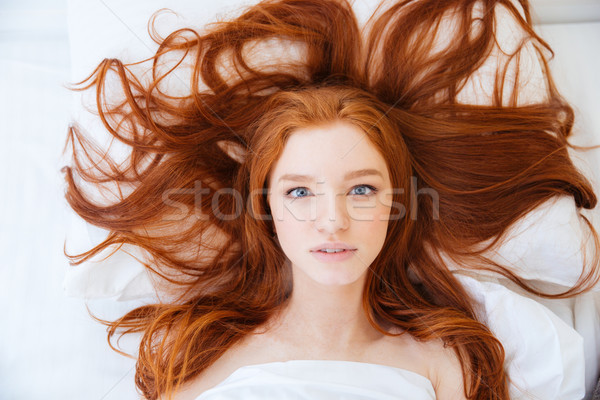 Woman with beautiful long red hair lying in bed  Stock photo © deandrobot