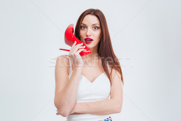 Beautiful woman holding red heel Stock photo © deandrobot