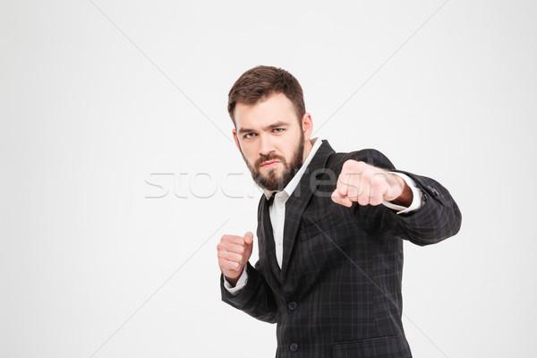 Businessman hitting at camera Stock photo © deandrobot