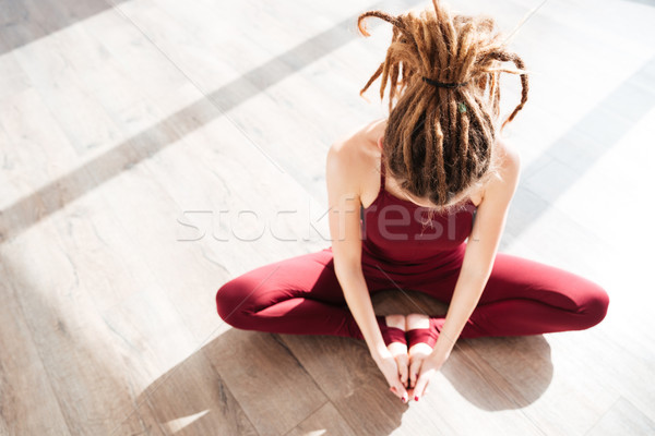 Modern young woman with dreadlocks sitting and doing yoga Stock photo © deandrobot