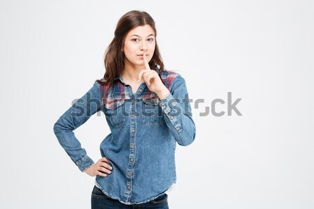 Attractive woman in jeans shirt standing and showing silence gesture  Stock photo © deandrobot