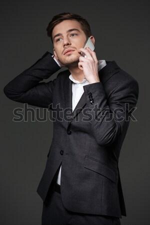задумчивый привлекательный молодые бизнесмен черный костюм говорить Сток-фото © deandrobot