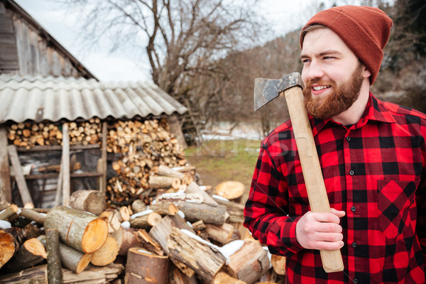 Smiling lumberjack holding axe Stock photo © deandrobot
