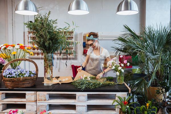 Cheerful woman florist enjoying creating bouquet in flower shop Stock photo © deandrobot