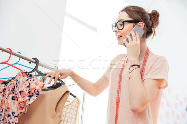 Stock photo: Happy woman fashion designer with measuring tape using cell phone