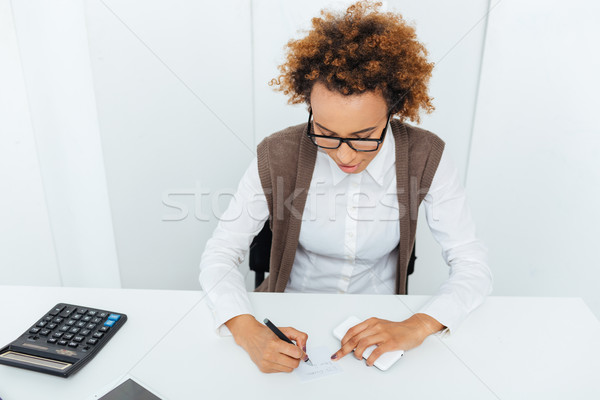 Curly african young woman accountant sitting and writing in office Stock photo © deandrobot