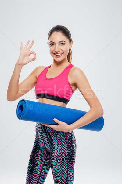 Woman holding yoga mat and showing ok sign with fingers Stock photo © deandrobot