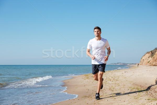 Happy sportsman running on the beach Stock photo © deandrobot