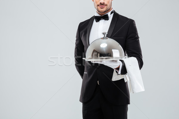 Butler in tuxedo and gloves holding silver tray with lid Stock photo © deandrobot