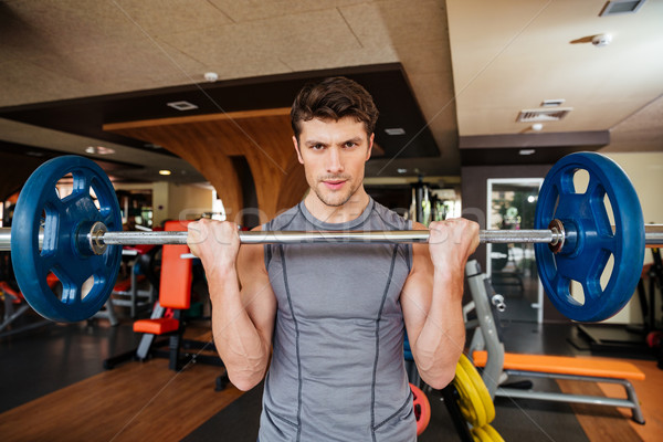 Attracitve young sportsman training using barbell in gym Stock photo © deandrobot