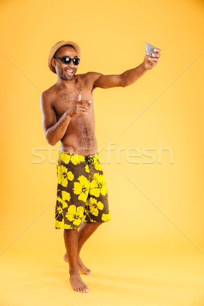 Happy man in swimwear making selfie photo on smartphone Stock photo © deandrobot