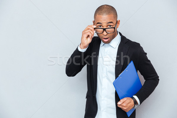 Surprised african businessman with blue folder looking over glasses Stock photo © deandrobot
