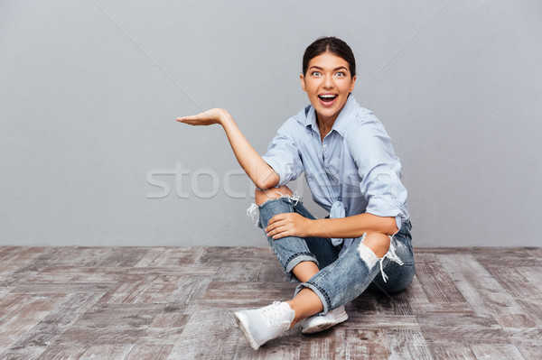 Happy smiling girl sitting and holding copyspace on palm Stock photo © deandrobot