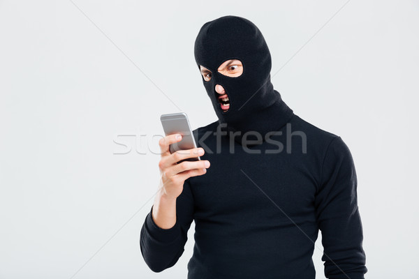 Angry young man in balaclava using cell phone Stock photo © deandrobot