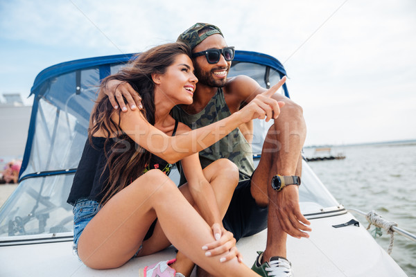 Couple hugging and pointing away on boat Stock photo © deandrobot