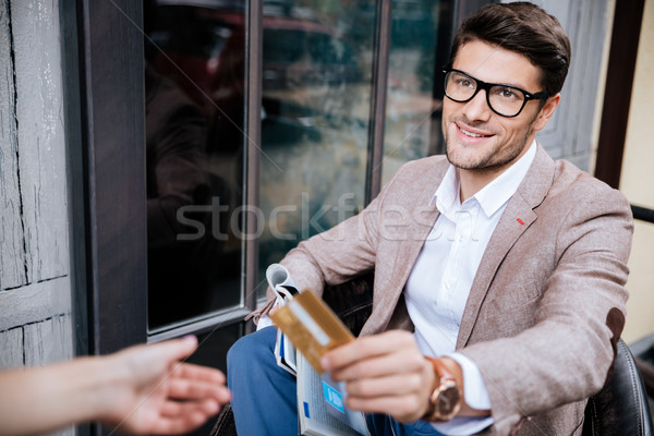 Cheerful young man paying by credit card in outdoor cafe Stock photo © deandrobot
