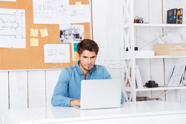 Pensive handsome bearded casual businessman sitting with laptop Stock photo © deandrobot