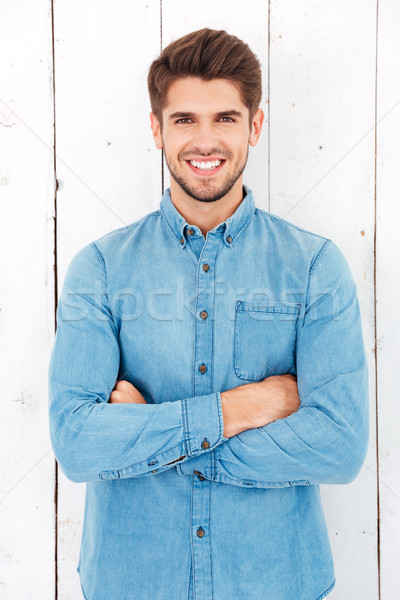 Portrait of a happy casual man standing with arms folded Stock photo © deandrobot