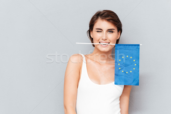 Happy woman holding european flag in teeth and winking Stock photo © deandrobot