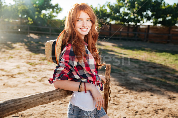 Cheerful woman cowgirl standing in village Stock photo © deandrobot