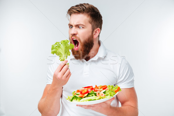 Young bearded man eating lettuce leaves Stock photo © deandrobot