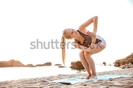 Portrait of a beautiful woman doing stretching exercises outdoors Stock photo © deandrobot